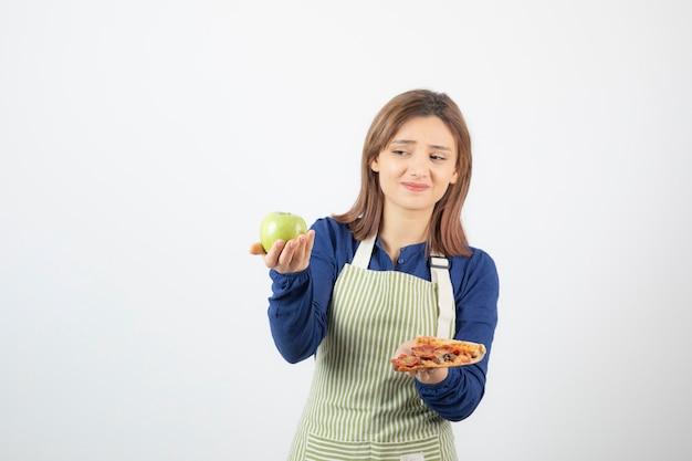Porträt einer frau in schürze, die versucht zu wählen, was sie apfel oder pizza essen soll?