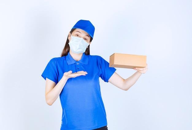 Porträt einer frau in uniform und medizinischer maske mit papierkasten