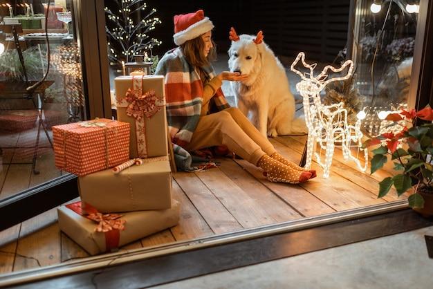 Porträt einer frau in weihnachtsmütze und plaid mit ihrem süßen hund, der auf der wunderschön dekorierten terrasse zu hause einen neujahrsurlaub feiert und den hund mit lebkuchen füttert