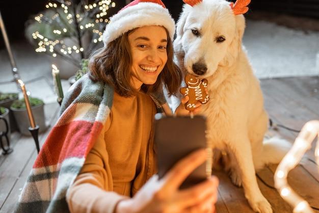 Porträt einer frau in weihnachtsmütze und plaid mit ihrem süßen hund, der zu hause neujahrsfeiertage feiert, hund mit lebkuchen füttert und ein selfie-foto macht