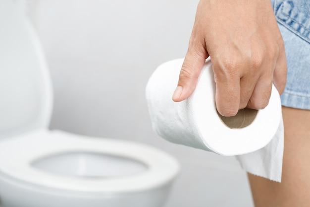 Porträt einer frau leidet an durchfall, sein magen ist schmerzhaft. schmerzen und probleme. hand halten seidenpapierrolle vor der toilettenschüssel. verstopfung im badezimmer. hygiene, gesundheitskonzept.