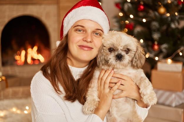Porträt einer frau mit angenehmem lächeln, die ihren kleinen süßen hund umarmt, weihnachtsmütze und weißen pullover trägt und in einem mit weihnachtsbaum und kamin dekorierten raum posiert.