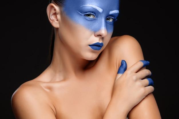 Porträt einer frau mit blauer farbe bedeckt