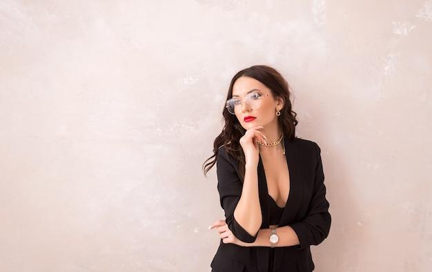 Porträt einer frau mit brille auf hellem hintergrund. ein ernstes mädchen in einem schwarzen anzug und einer brille schaut hinein.