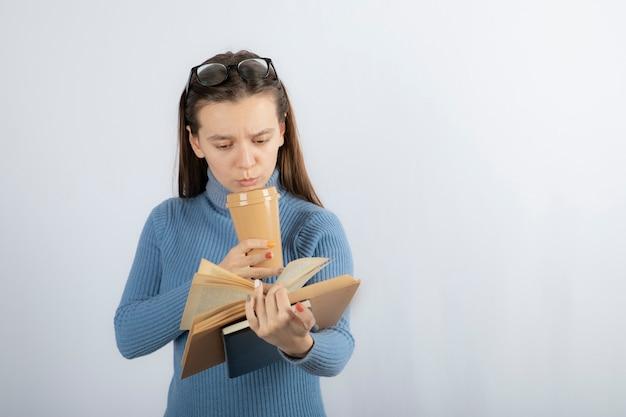 Porträt einer frau mit brille, die ein buch mit einer tasse kaffee liest.