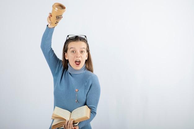 Porträt einer frau mit brille, die ein buch und eine tasse kaffee hält.