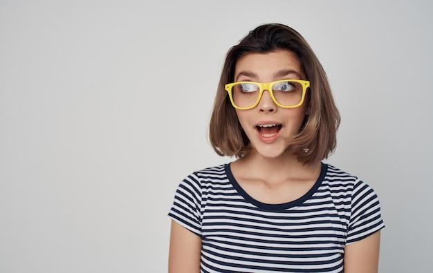 Porträt einer frau mit brille und einem gestreiften t-shirt auf einem roten rock der grauen hintergrundmode. hochwertiges foto
