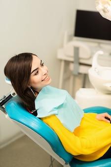 Porträt einer frau mit dem toothy lächeln, das am zahnmedizinischen stuhl im zahnmedizinischen büro sitzt