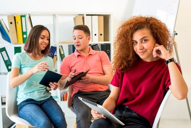 Porträt einer frau mit den gelockten haaren, die auf dem stuhl hält digitale tablette mit ihren freunden am hintergrund sitzen