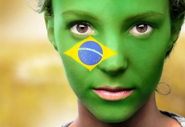 Porträt einer frau mit der flagge brasiliens im gesicht