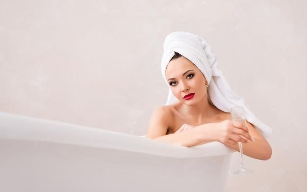 Porträt einer frau mit einem handtuch auf dem kopf im badezimmer. ein mädchen mit make-up liegt im badezimmer.