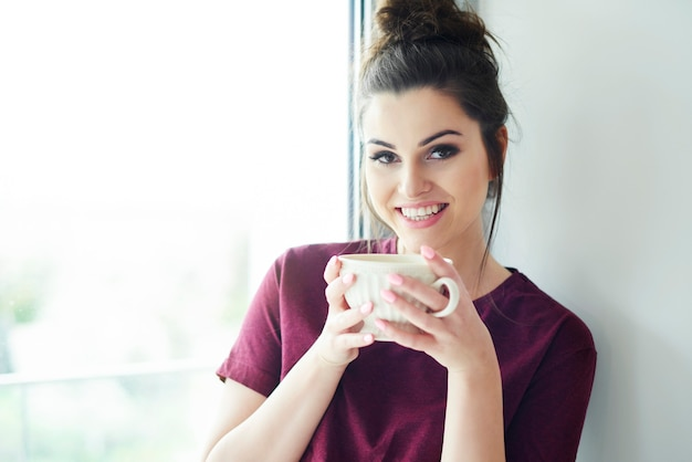 Porträt einer frau mit einer tasse kaffee am morgen