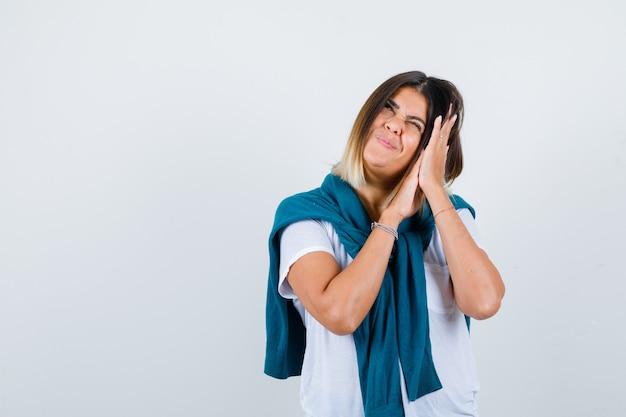 Porträt einer frau mit gebundenem pullover, der sich auf handflächen als kissen im weißen t-shirt lehnt und eine positive vorderansicht sieht