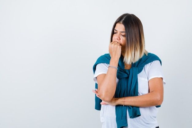 Porträt einer frau mit gebundenem pullover, die emotional die faust in weißem t-shirt beißt und nachdenkliche vorderansicht schaut