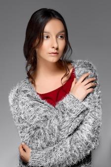 Porträt einer frau mit glattem haar, das in einen flauschigen pullover eingewickelt wird