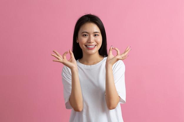 Porträt einer frau mit hand in ordnung, gestikulierend, isoliert auf rosa