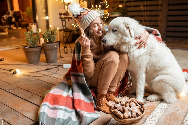 Porträt einer frau mit ihrem süßen hund, die neujahrsfeiertage feiert, zusammensitzt und lebkuchen auf der wunderschön dekorierten terrasse zu hause isst