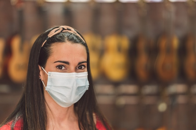Porträt einer frau mit maske in einem instrumentenladen voller gitarren