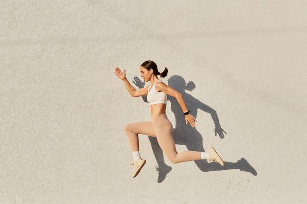 Porträt einer frau mit perfektem körper, die in die luft springt und ein weißes oberteil und beige leggins trägt