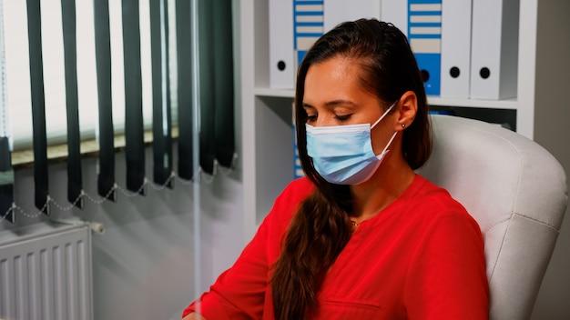 Porträt einer frau mit schutzmaske, die am computer schaut und arbeitet. mitarbeiter in einem neuen normalen büroarbeitsplatz, der auf der computertastatur tippt und auf den desktop schaut