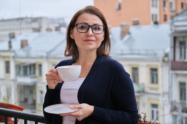 Porträt einer frau mittleren alters mit brille, strickjacke, mit tasse tee auf offenem balkon in der stadt. hintergrund städtische architektur, gebäude, lächelnde weibliche blicke in die kamera