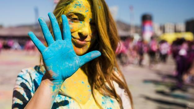 Porträt einer frau, welche die kameravertretung gemalte blaue hand betrachtet