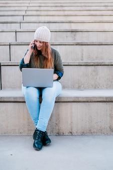 Porträt einer freiberuflichen frau, die laptop und smartphone benutzt, während sie auf der treppe in der stadtstraße sitzt
