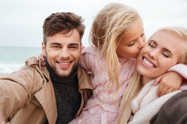 Porträt einer freudigen familie mit einer kleinen spielenden tochter