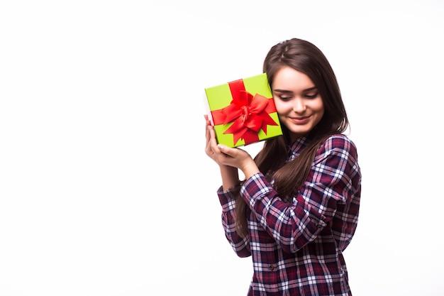 Porträt einer freudigen jungen frau gekleidet im roten kleid, das stapel von geschenkboxen hält und lokalisiert über weißem hintergrund feiert