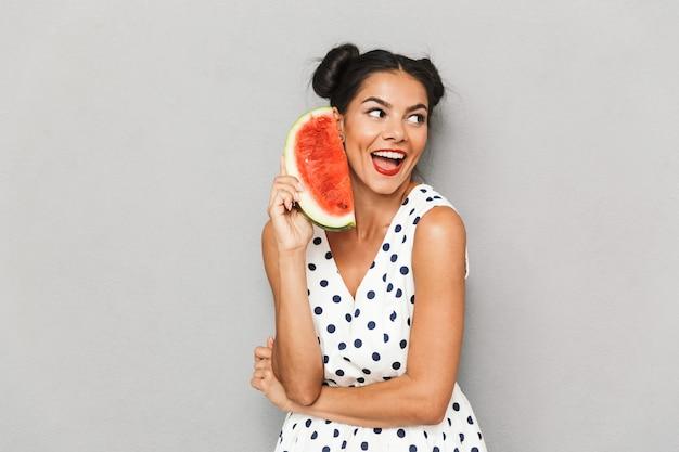 Porträt einer freudigen jungen frau im sommerkleid lokalisiert, wassermelonenscheibe haltend