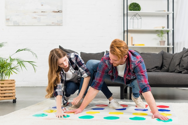 Porträt einer freundin, die versucht, hände und füße auf farbpunktspiel zu berühren