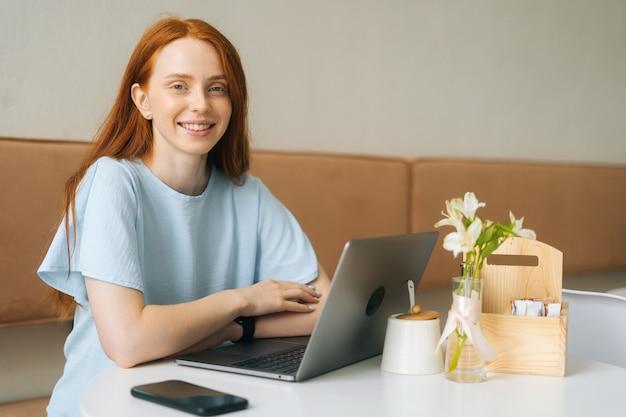 Porträt einer fröhlichen, attraktiven jungen frau, die mit laptop und telefon im café mit warmem tageslicht am tisch sitzt und die kamera betrachtet. hübsche kaukasische dame der rothaarigen entfernt, die arbeitet oder studiert.