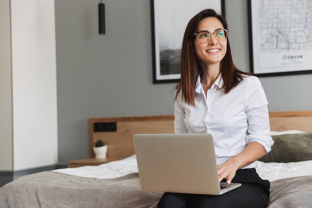 Porträt einer fröhlichen erwachsenen geschäftsfrau im formellen anzug, die auf dem laptop tippt, während sie auf dem bett in der wohnung sitzt