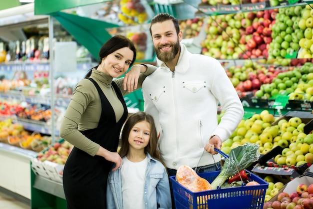 Porträt einer fröhlichen familie, die mit einem vollen wagen im supermarkt im gemüse steht