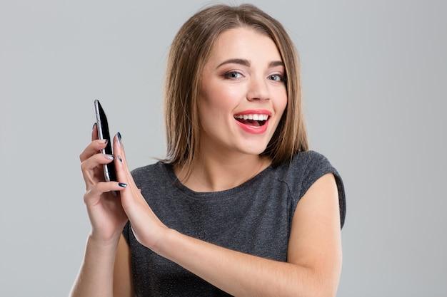 Porträt einer fröhlichen frau, die das mikrofon auf dem smartphone bedeckt und die kamera isoliert auf einem weißen betrachtet