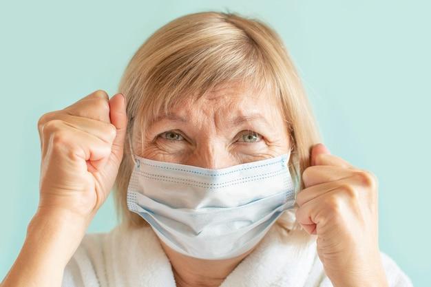 Porträt einer fröhlichen frau, die eine medizinische maske wegen der coronavirus-epidemie trägt.