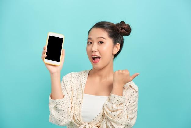 Porträt einer fröhlichen frau, die smartphonebildschirm zeigt