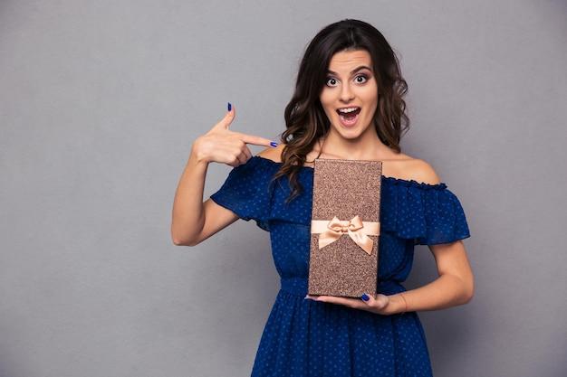 Porträt einer fröhlichen frau mit geschenkbox über grauer wand und