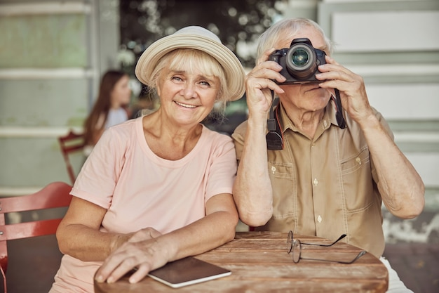 Porträt einer fröhlichen frau mit sonnenhut, die mit ihrem mann an einem tisch sitzt