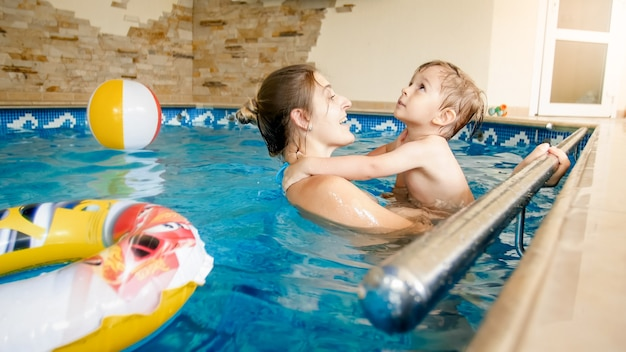 Porträt einer fröhlichen, fröhlichen jungen mothete mit einem 3-jährigen kleinkindjungen, der im pool im haus spielt kind lernt schwimmen mit elternteil. familie hat spaß im sommer