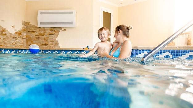 Porträt einer fröhlichen, fröhlichen jungen mothete mit einem 3 jahre alten kleinkindjungen, der im pool im haus spielt