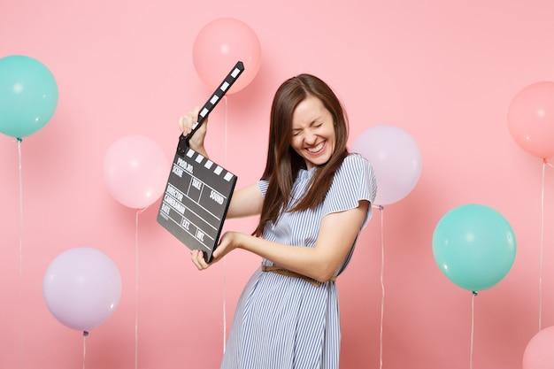 Porträt einer fröhlichen, glücklichen jungen frau mit geschlossenen augen im blauen kleid, die klassische schwarze filmklappe auf pastellrosa hintergrund mit buntem luftballon hält. geburtstagsfeier konzept.