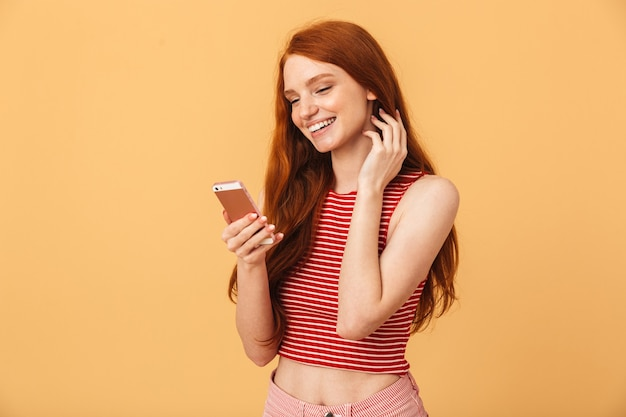 Porträt einer fröhlichen, glücklichen, süßen, jungen hübschen rothaarigefrau, die isoliert über gelber wand posiert und mit dem handy chattet.