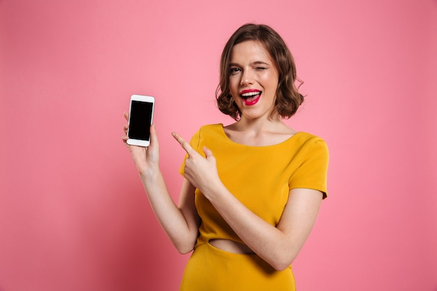 Porträt einer fröhlichen hübschen frau, die finger auf leer zeigt