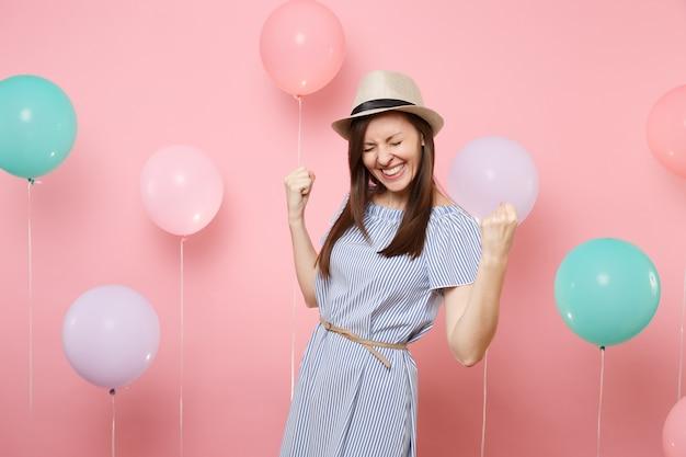 Porträt einer fröhlichen hübschen jungen frau, die strohsommerhut und blaues kleid trägt, tun siegergeste, die ja auf rosafarbenem hintergrund mit buntem luftballon sagt. geburtstagsfeier-partyleute aufrichtige gefühle.