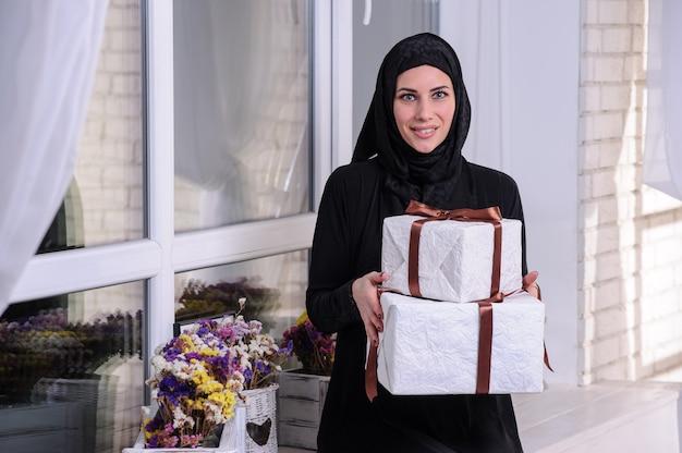 Porträt einer fröhlichen jungen arabischen frau, die einen stapel geschenkkartons einzeln auf grauem hintergrund zeigt