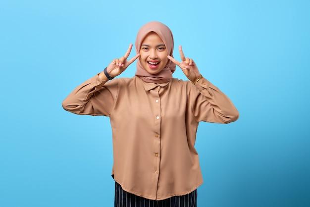 Porträt einer fröhlichen jungen asiatin, die friedenszeichen mit den fingerhänden über blauem hintergrund macht