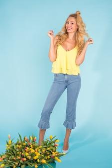 Porträt einer fröhlichen jungen blonden frau, die nahe schachtel tulpen auf blauer oberfläche aufwirft