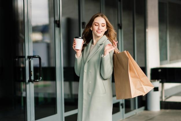Porträt einer fröhlichen jungen dame mit einkaufstüten im freien