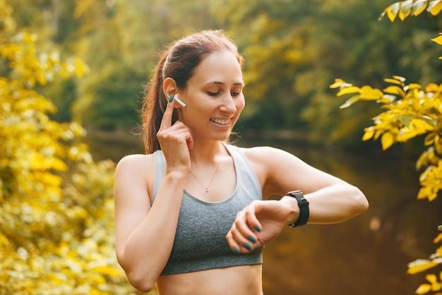 Porträt einer fröhlichen jungen frau des sports im freien bei sonnenuntergang mit ohrstöpseln und mit blick auf die smartwatch